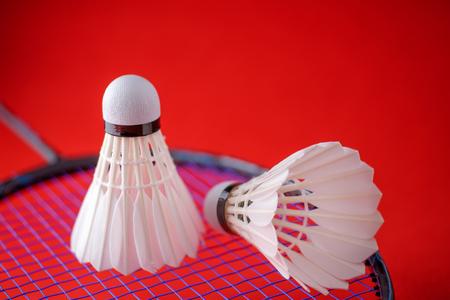 shuttlecock: Shuttlecocks on badminton racket against red background.