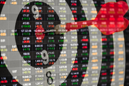 Double exposure of Dart arrow hitting in the target center of dartboard and Stock market board on a monitor. Stock Photo