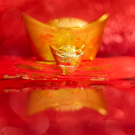 Chinese New Year Decoration, Gold ingots and red packet or ang pow with red bokeh background. Stock Photo