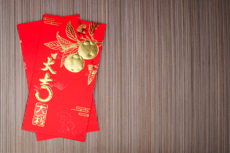 Red envelope with the chinese characters for a lot of luck and fortune on bamboo background, Chinese new year festival.