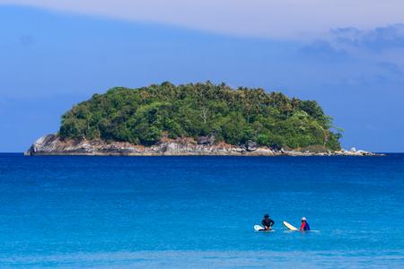 Surfers sitting on surfboard in water at the beach. Kata Beach, Phuket, Thailand.