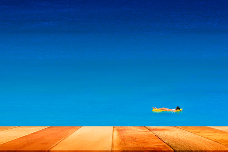 Wood plank and girl in white bikini relax on air bed in the blue sea. Kata Beach, Phuket, Thailand.