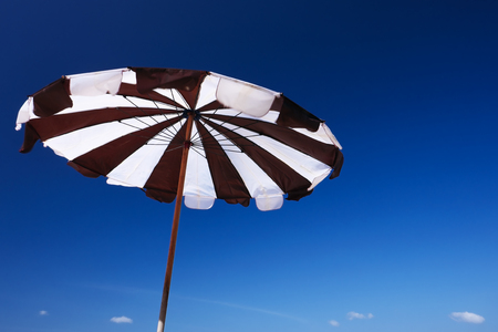 Beach umbrella on the sky background.