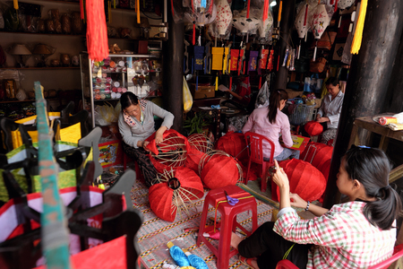 HOI AN, VIETNAM - MARCH 02, 2017 : Vietnamese woman making lanterns in a shop in Hoi An, Vietnam.