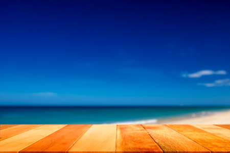 Wood plank with blurred sea and sky background. Concept of beach in summer.