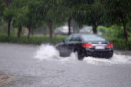 heavy: Blurred image of Car driving on a flooded road. Bangkok, Thailand.