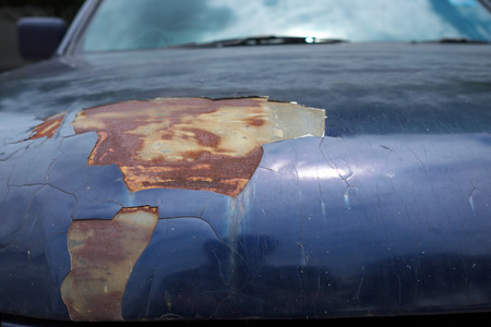 corrosion: Car hood with a hole from rust and corrosion.