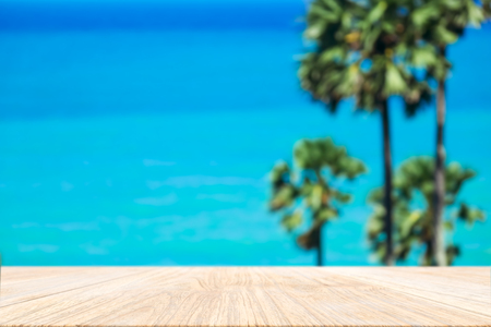 Wood plank with blurred sea and sugar palm tree background. Concept of beach in summer.