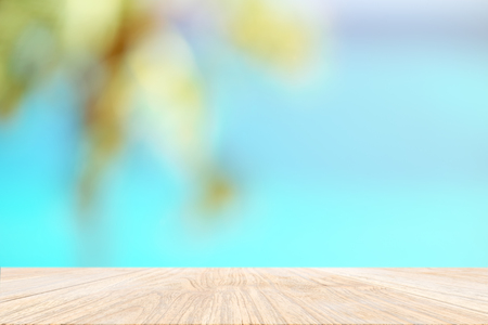 Wood plank with blurred sea and palm tree background. Concept of beach in summer.