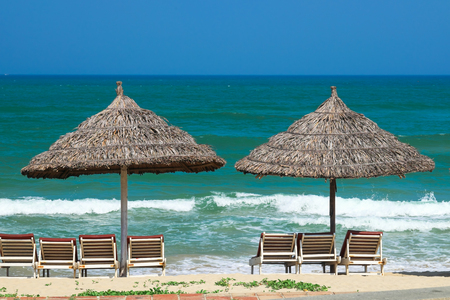 Beach umbrellas and deck chairs in front of the My Khe beach in Da Nang, Vietnam.