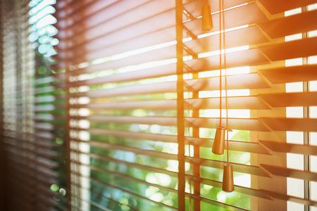 Żaluzje drewniane z promieniami słonecznymi.