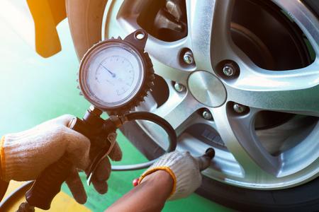 자동차 정비공 타이어 압력을 검사합니다.