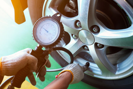 Car mechanic checking the tire pressure. Banco de Imagens - 87634777