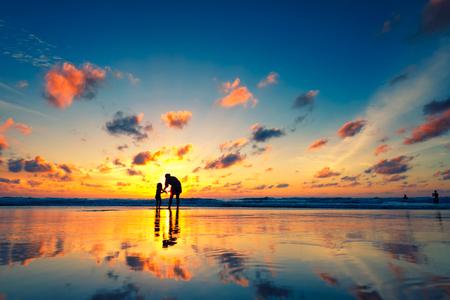 Moeder met haar dochter op het strand bij zonsondergang. Vintage kleurstijl.