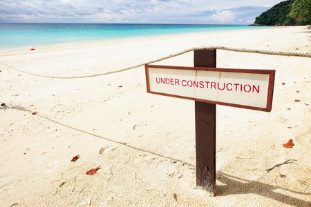 Under Construction sign on the beach.