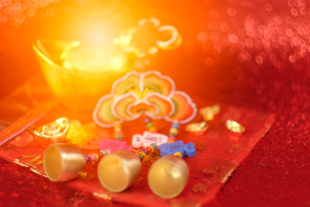 Blurred image of Chinese New Year Decoration, Gold ingots and auspicious ornaments on red bokeh background. Stock Photo
