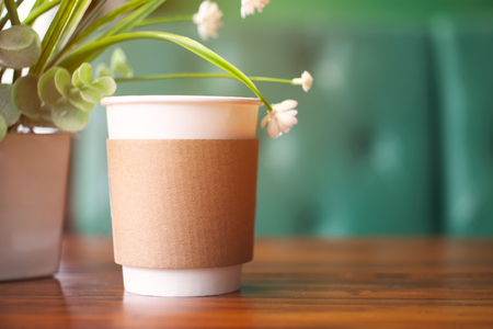 Paper cup of coffee on wooden table. Reklamní fotografie