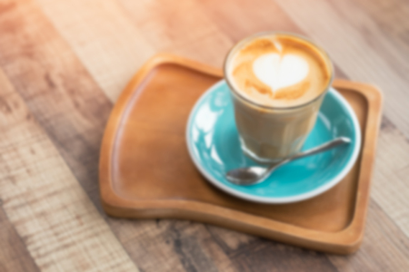Blurred image of Late art coffee with heart shape on wood table background. Top view.