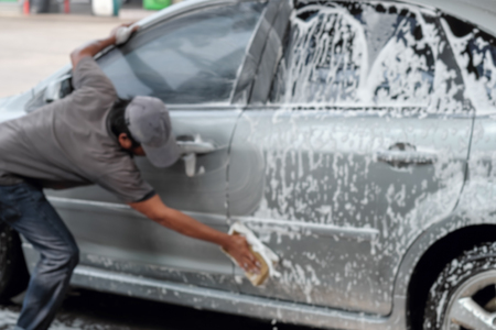 Blurred image of worker washing the  car at car wash service center.
