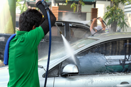 Worker washing the  car  with high pressure water jet at car wash service center.