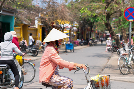 Vietnamese woman cycling at Hoi An old town, Vietnam.