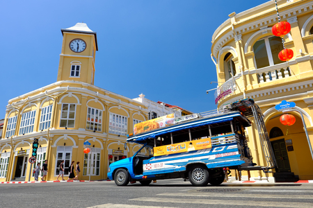 PHUKET, THAILAND - MARCH 01, 2018:  The local wooden passenger mini bus and  Renovated Sino Portuguese Architecture in Phuket old town against blue sky. Editorial