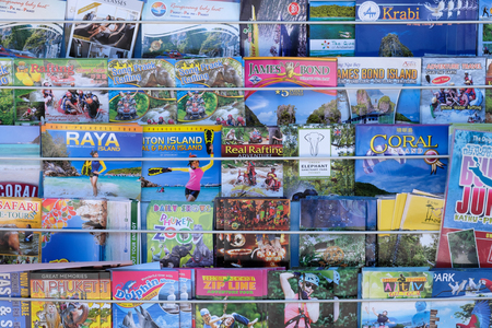 PHUKET, THAILAND - MARCH 01, 2018: Various of the colorful tourism brochures for tourists along the street in Phuket, Thailand.
