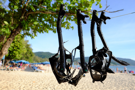 Snorkels and masks hanging on the rope service for tourist at the beach.