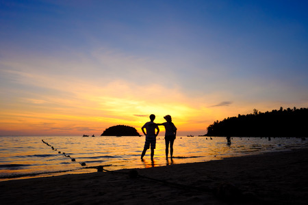 Silhouette of couple at the sunset Kata beach, Phuket, Thailand
