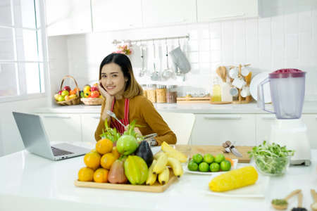 Young asian woman watching online training in the kitchen at home, healthy lifestyle.