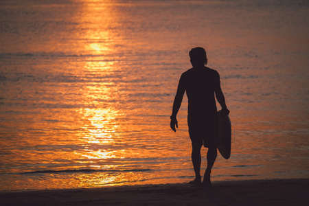 Silhouette of man with surfboard on sunset beach with sun light background. Imagens - 166065503