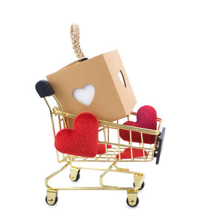 Shopping cart with gift packaging and red heart isolated on white background. Valentine's Day and online shopping concept.