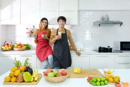 Happy young asian couple eating healthy food in kitchen at home, healthy lifestyle. Imagens