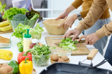 Young couple preparing a meal chopping vegetables in kitchen at home, healthy lifestyle.