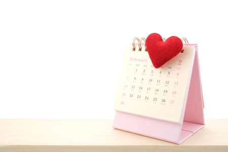 February Calendar 2021 page and red heart on wooden desk isolated white background, Valentine's Day Concept.