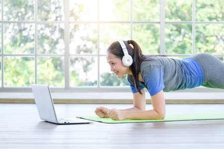 Asian girl doing plank while watching online tutorial on laptop, training in living room at home. Imagens