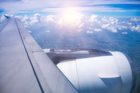 window view of airplane wing and engine in flight with clouds on sky background. Imagens