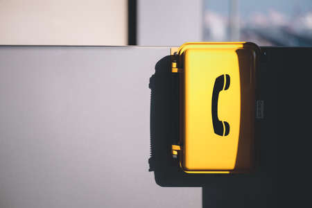 The yellow emergency phone on wall in train station.