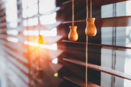 Wooden blind on the window with sun rays. Office blinds. Wooden shutters blind. Vintage color style.
