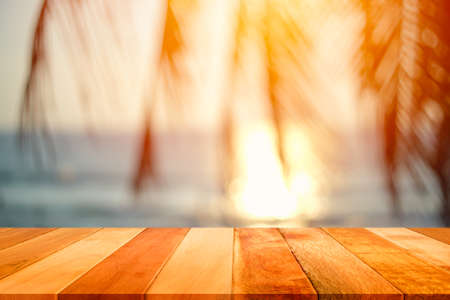 Wood plank with blurred sea and coconut tree background. Concept of beach in summer. Imagens