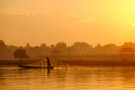 Local fishermen in Taung Tha Man lake near U Bein bridge in early morning at sunrise. Mandalay, Myanmar (Burma). Imagens