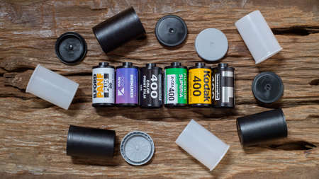 BANGKOK, THAILAND - FEBRUARY 16, 2021: Top view of many photographic roll films 35 mm on old wooden table before sending to the film shop for develop.