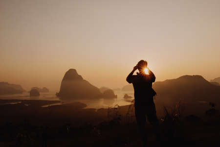 Young man taking picture of sun rise at Samed Nang Chee mountain view point, Phang Nga Province, Thailand.