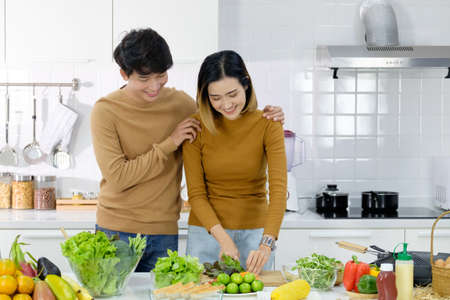 Asian young couple preparing a meal chopping vegetables in kitchen at home, healthy lifestyle.