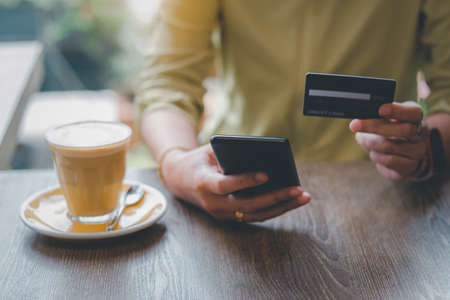 Women are holding credit card and using mobile phone to pay for online shopping in a coffee shop. Online payment Concept.