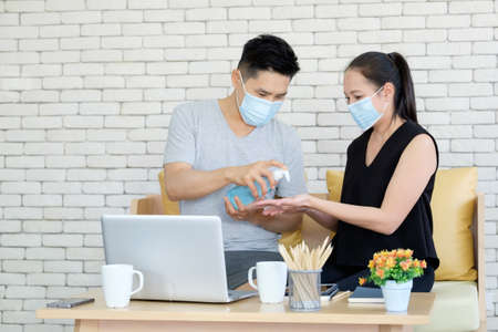Asian husband wearing mask and giving alcohol gel hand sanitizer to his wife Imagens