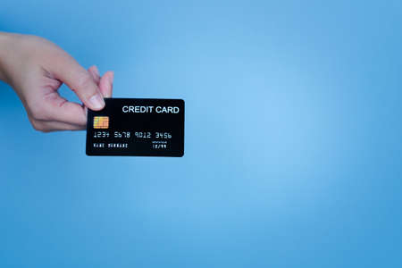 Woman's hand holding the black credit card on cerulean background for shopping online. Imagens