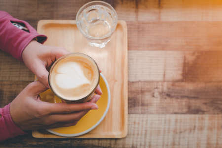 Top view of female's hand holding cup of coffee on wooden table.