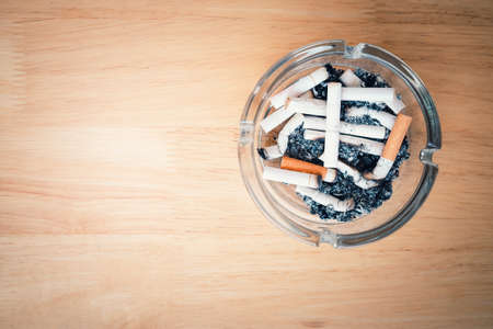 Top view of cigarette stubs and ash in a glass ashtray on wooden table. Imagens