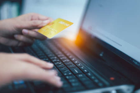 Woman's Hands holding credit card and using laptop. Online shopping and payment concept.